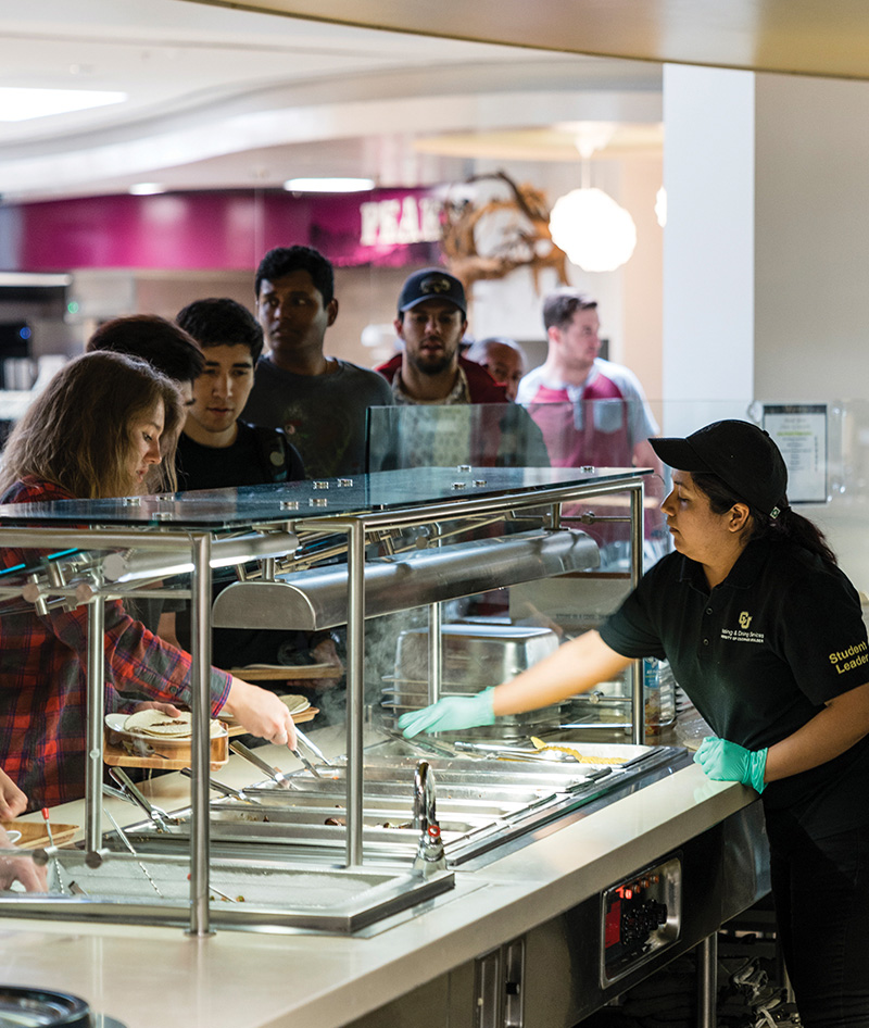 Campus dining employee serving students