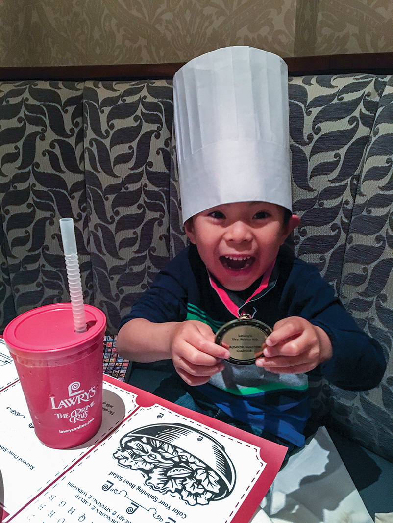 Kid in a booth with a chefs hat on