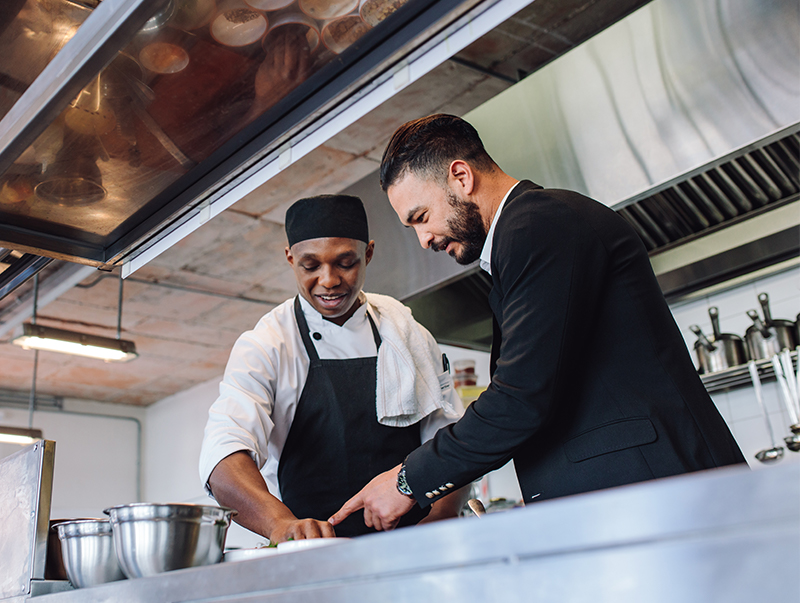 Restaurant manager working with staff member in kitchen